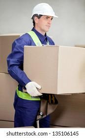 Portrait of foreman lifting cardboard box at warehouse