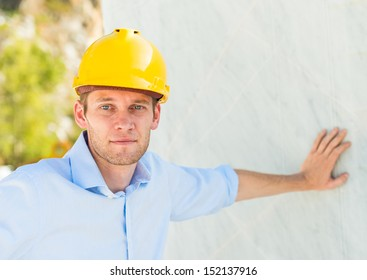 portrait of a foreman near a big marble block