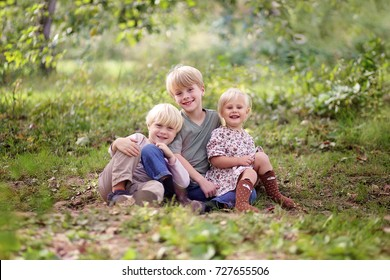 A portrait in the forest of three happy, smiling young children, an eight year old boy, his baby sister and his 5 year old little brother.