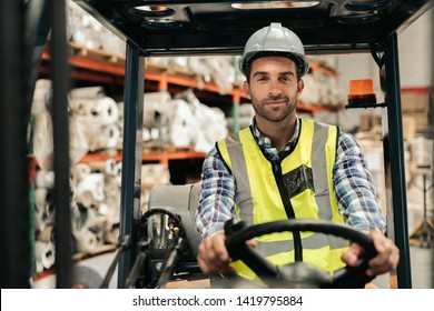 Portrait of a forklift driver wearing a hardhat and vest while moving stock around the floor of a carpet warehouse