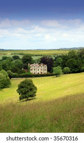 Portrait format image of a country manor looking across an open rolling field to the foreground. Located in rural Wiltshire UK in a small village called Wishord Cum lake.