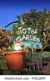 A portrait format image of a terracotta coloured flower pot and garden gnome in front of a garden fork and hand painted wooden sign with text spelling 'to the garden'.
