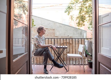 Portrait of a forty something man enjoying his day in a European city, sitting on a balcony. He has kind eyes and long, curly hair. He is enjoying a glass of red wine