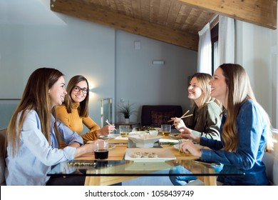 Portrait of four beautiful young women eating japanese food at home.