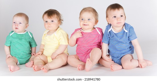 Portrait of four beautifull toddlers sitting in line