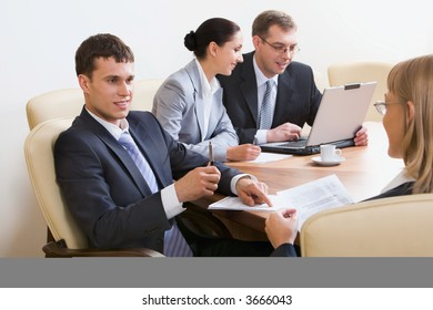 Portrait of four businesspeople discussing different questions sitting in white comfortable chairs at the table with an opened laptop, documents and cup on it