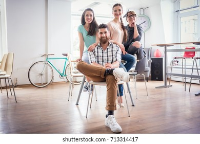 Portrait of four co-workers smiling and looking at camera while wearing cool casual clothes, during work in the shared office space of a modern hub for freelancers and young entrepreneurs