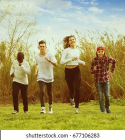 Portrait of four friends running on field in sunny day