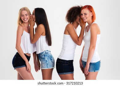 Portrait of a four girls gossiping isolated on a white background