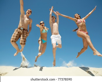 Portrait of four happy friends jumping energetically over sandy shore