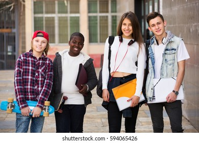 Portrait of four happy teenage students close to university