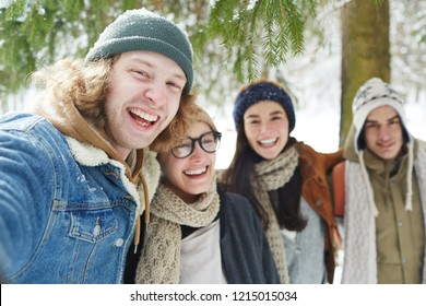 Portrait of four happy young people enjoying time in winter resort and laughing merrily looking at camera, focus on man in front