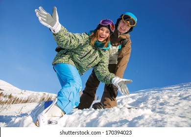 Portrait of four laughing girls in ski goggles sitting on snow