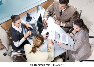 Portrait of four professionals sitting at the table and discussing business ideas in the office