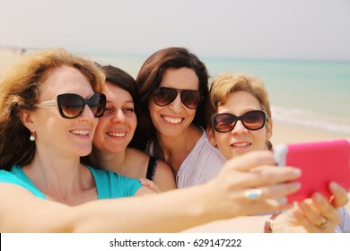 Portrait of four smiling 40 years old women outdoors