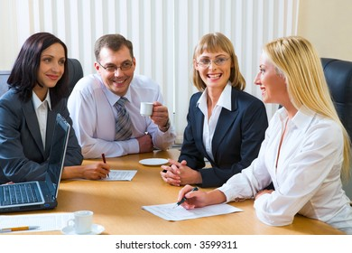 Portrait of four smiling discussing businesspeople sitting around the table with an opened laptop, documents and cups on it