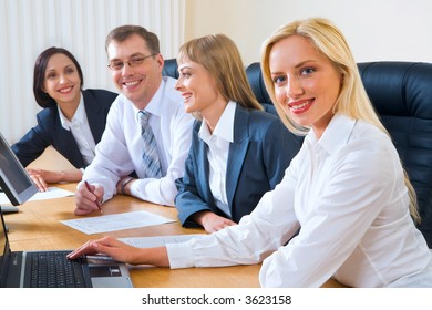 Portrait of four smiling discussing businesspeople sitting at the table in a row with an opened laptops and documents on it