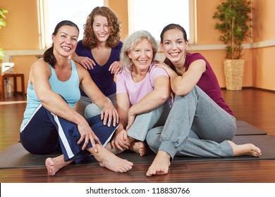 Portrait of four smiling happy women sitting in a fitness center