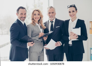 Portrait of four stylish, attractive, confident business people using, having gadget, paper, clipboard, dairy, organizer, standing in work place, station, looking at camera, wearing classic suits