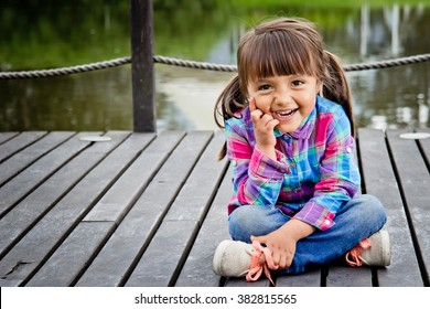 Portrait of four year old girl siiting on a city park and smiling at camera.