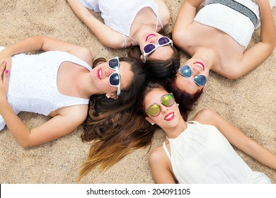 Portrait of foursome teen girlfriends laying on beach together and joining heads.