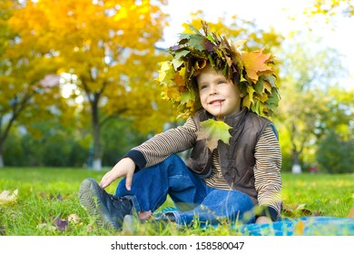 Portrait of four-year-old boy who sits on grass in a wreath from autumn leaves
