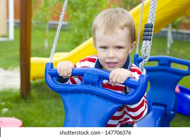 portrait of the four-year-old kid on a swing