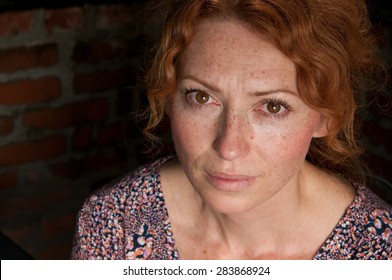 portrait of freckled woman bloodshot eyes dark background