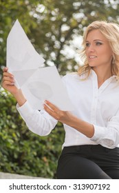 Portrait freelance lady comparing the documents. Beautiful woman working oudoors. She is holding papers in front of her.