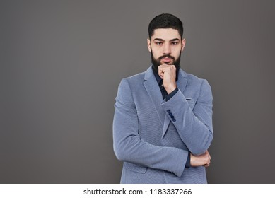 Portrait of freelancer man with beard in jacket standing against gray backdrop.