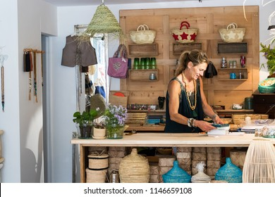 Portrait of french blonde mature woman working happy at her handmade gifts store in France, entrepreneur concept.