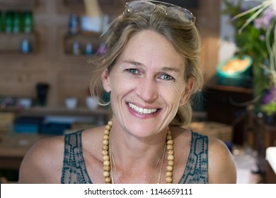Portrait of french blonde mature woman smiling in her handmade gifts store in France, entrepreneur concept.