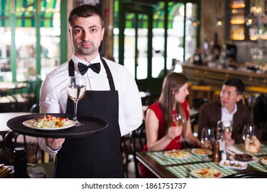 Portrait of frendly male waiter who is standing with tray in restaurant.