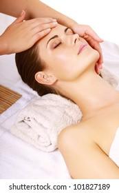 Portrait of fresh and beautiful brunette woman taking head massage