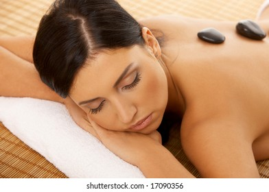 Portrait of Fresh and Beautiful brunette woman taking stone therapy