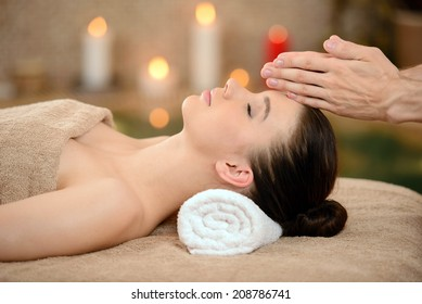Portrait of Fresh and Beautiful brunette woman taking head massage isolated on background spa salon