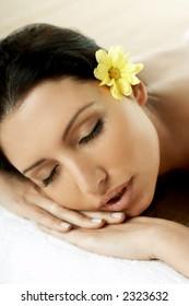 Portrait of Fresh and Beautiful brunette woman laying on bamboo mat around yellow flowers