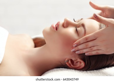 Portrait of fresh and beautiful brunette woman taking head and face massage