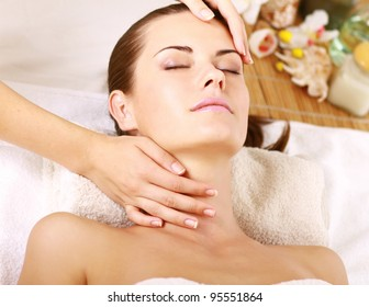 Portrait of Fresh and Beautiful brunette woman taking head massage isolated on white background