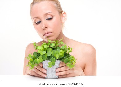Portrait of Fresh and Beautiful woman with the green plant and eyes closed