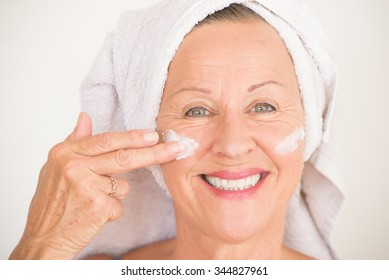 Portrait friendly attractive mature woman with towel and protective skin care creme and moisturizer lotion on happy smiling face, bright background.