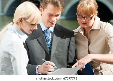 Portrait of friendly business team looking at document in man?s hands and talking