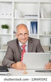 portrait of a friendly businessman sitting at desk with laptop