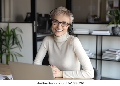 Portrait of friendly call center agent wear headset with microphone working sit at desk smile look at camera. Financial advisor helpline specialist consult clients distantly, on-line tutoring concept