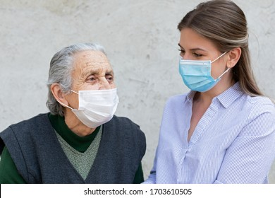 Portrait of friendly caregiver posing with elderly ill woman wearing surgical mask because of covid-19 pandemic