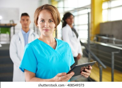 Portrait of a friendly caucasian female doctor and team in bright modern office