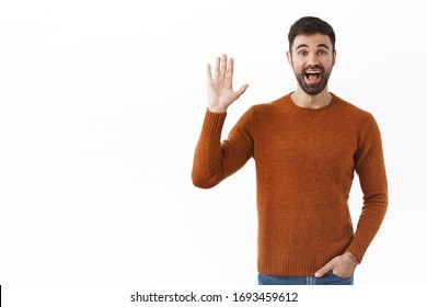Portrait of friendly cheerful bearded man waving hand at camera, saying hi, greeting person with happy smile, casual meeting of friends, hello gesture, standing white background