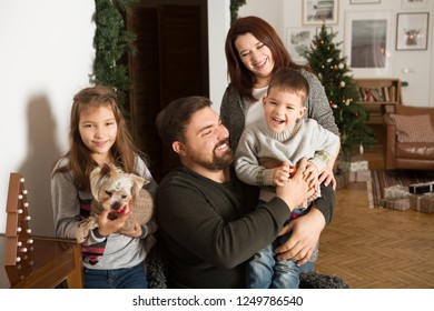 Portrait of friendly family playing, embrace and laugh on Christmas evening. Christmas holiday. Christmas family portrait.