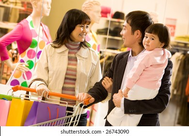 Portrait of friendly family shopping together with shop window at background