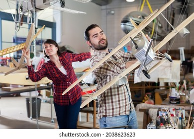Portrait of friendly female and male hobbyists with plane models created by them in aircraft workshop